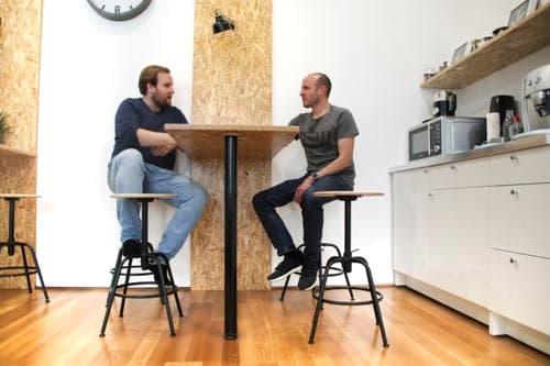 Zwei Mitarbeiter in der Küche beim Kaffee trinken