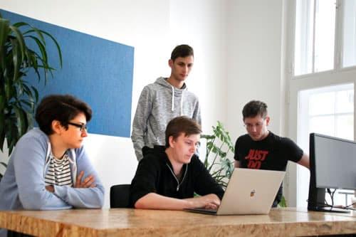 Mehrere Mitarbeiter von Alanda versammelt im Halbkreis vor einem Laptop